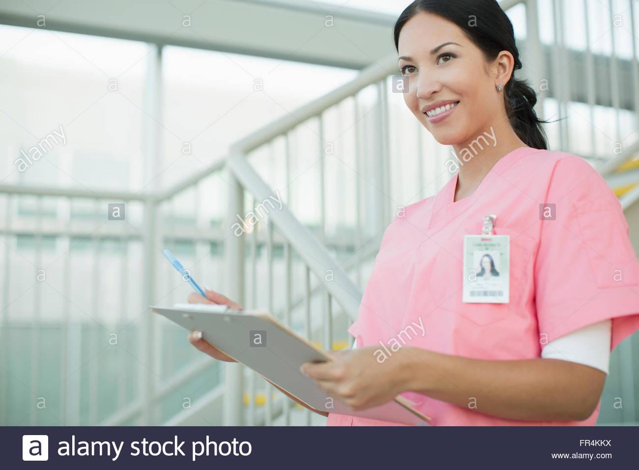 hübsche Krankenschwester stehend mit Diagramm in medizinischen Einrichtung Stockbild