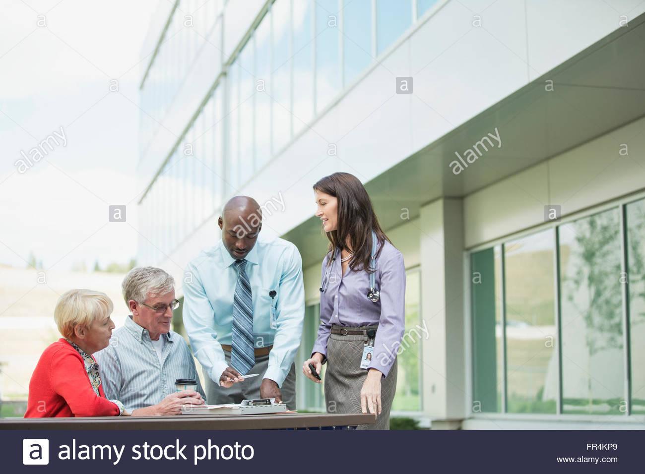 Älteres Paar im Gespräch mit Ärzten außerhalb der medizinischen Einrichtung Stockbild