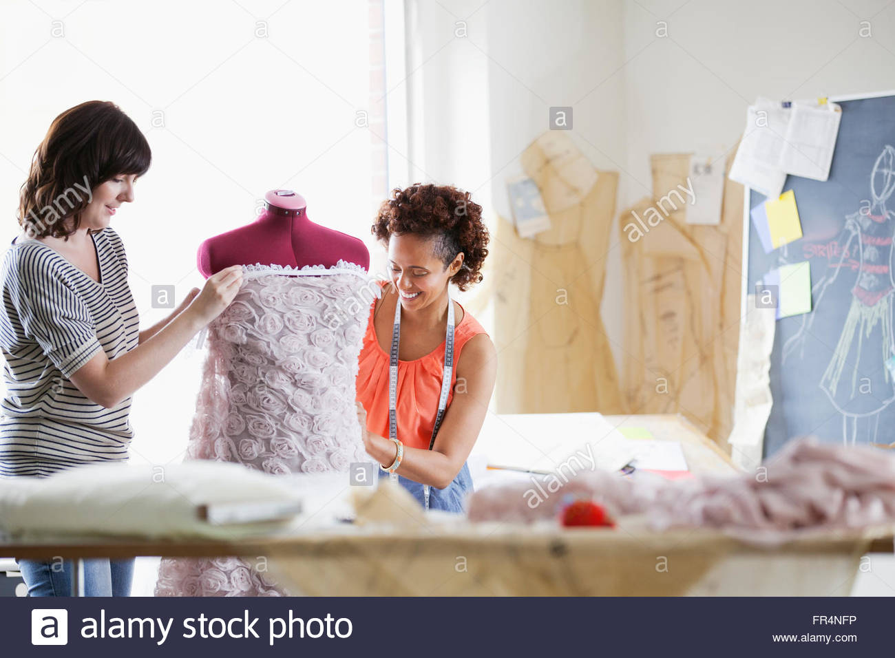 Kleid von Designer arbeiten gemeinsam an der Schneiderpuppe Stockbild