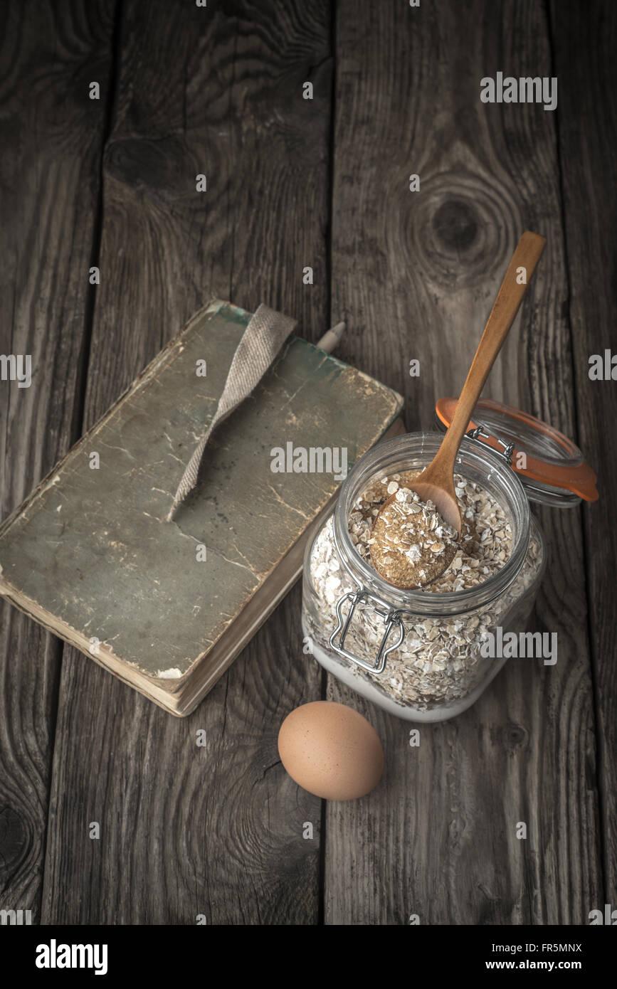Buch der Rezepte und Zutaten für Cookies auf einem Holztisch vertikale Stockbild