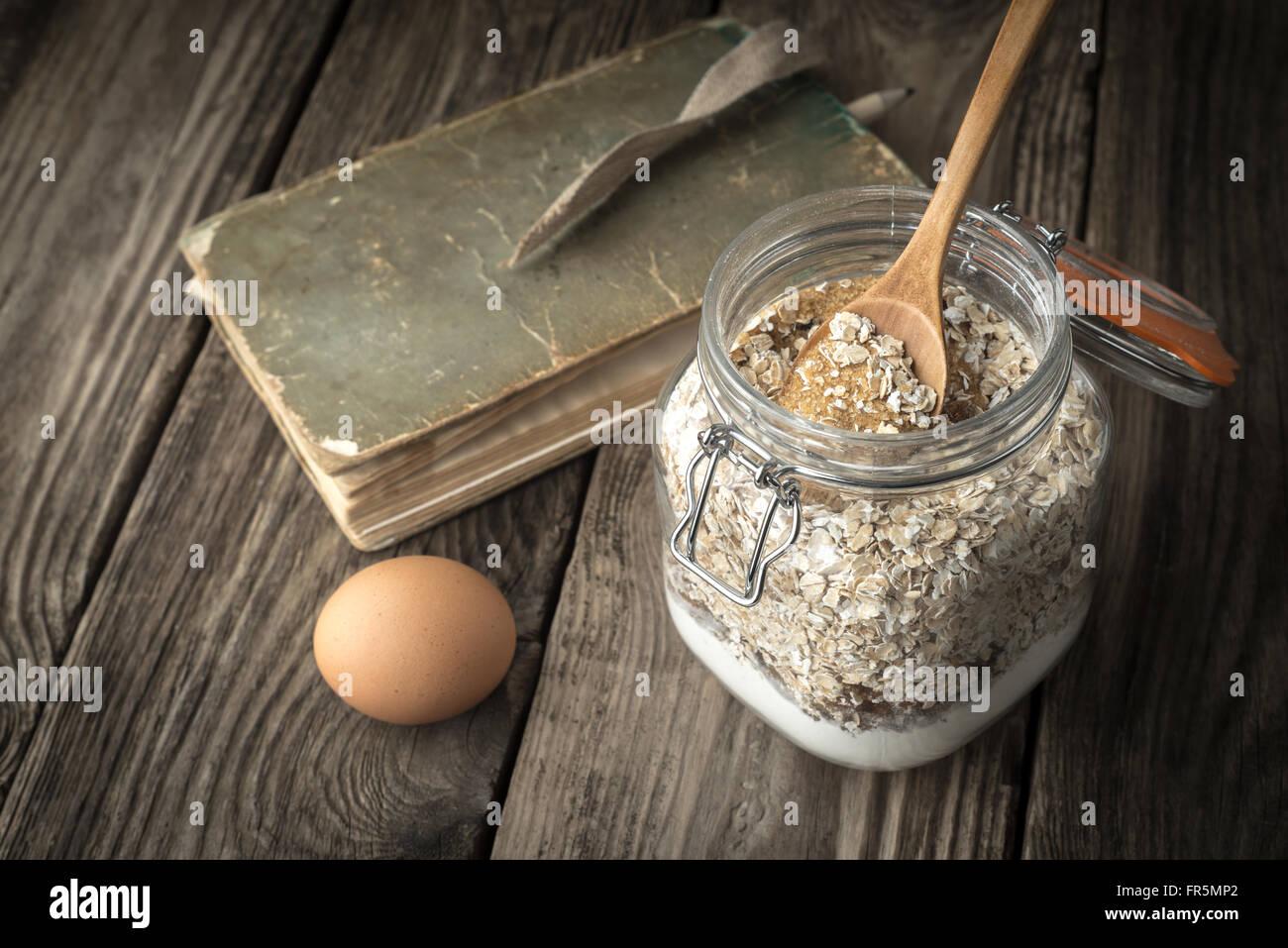 Buch der Rezepte und Zutaten für Cookies auf einem Holztisch horizontale Stockbild