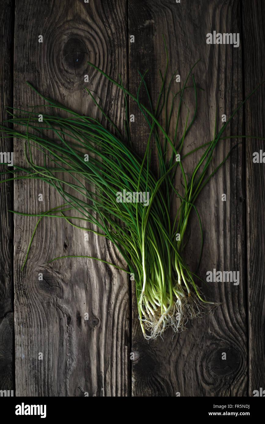 Stiele der grünen Zwiebeln auf einem Holztisch vertikale Stockbild