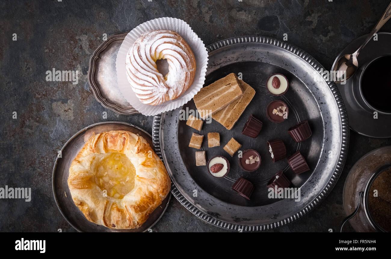 Süßigkeiten, Kuchen und Kaffee auf einem horizontalen grauen Stein Stockfoto
