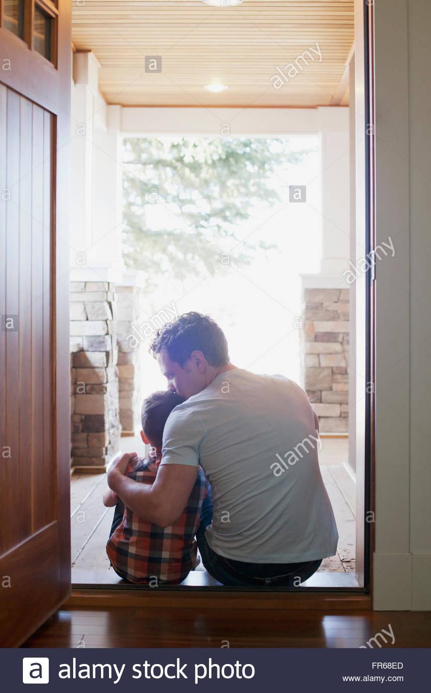 Vater und Sohn sitzen in Tür Stockfoto