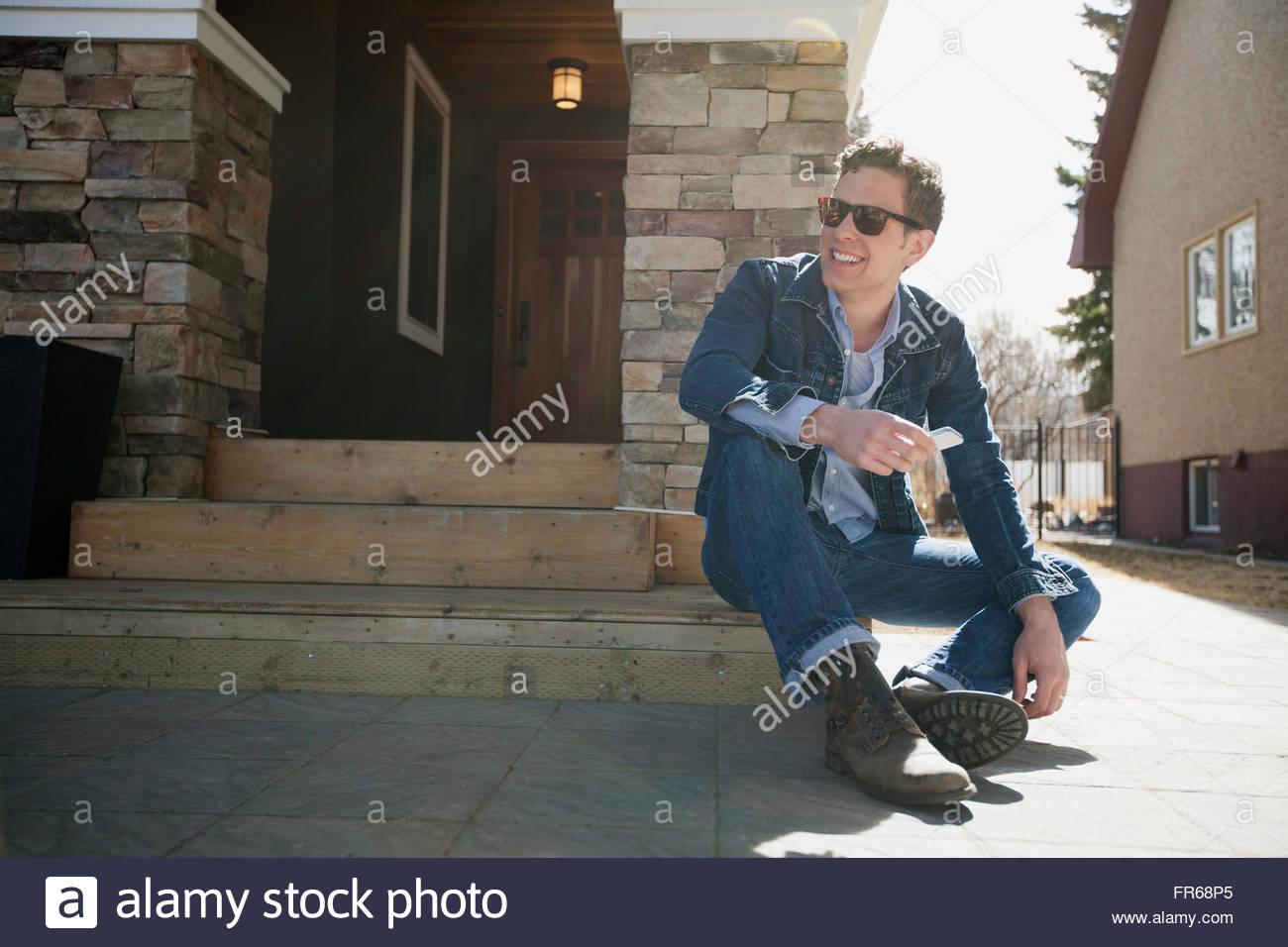 attraktiver Mann sitzt auf der Eingangstreppe des Wohnsitzes Stockbild