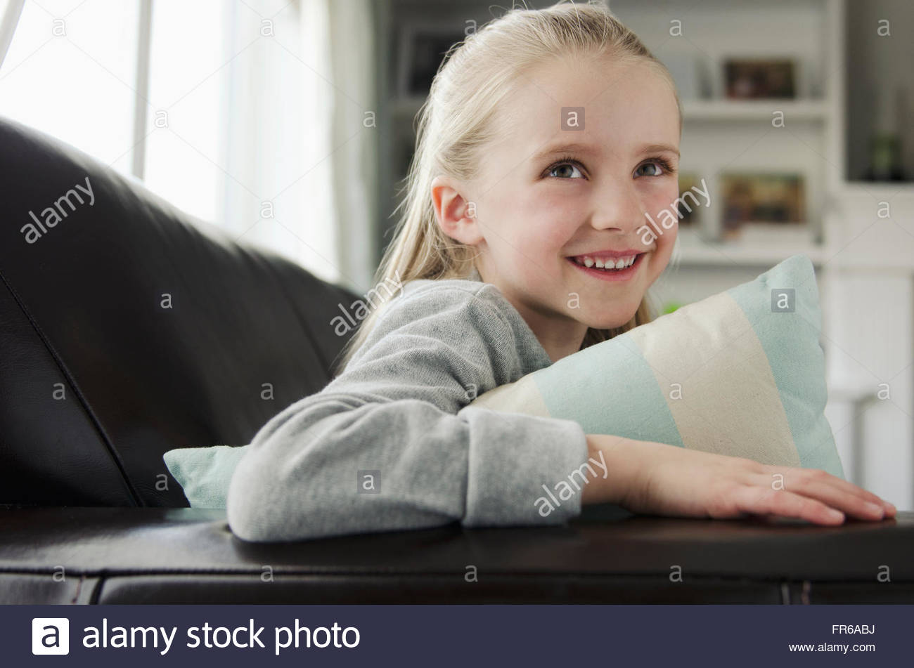 Porträt der süße junge blonde Mädchen auf couch Stockbild