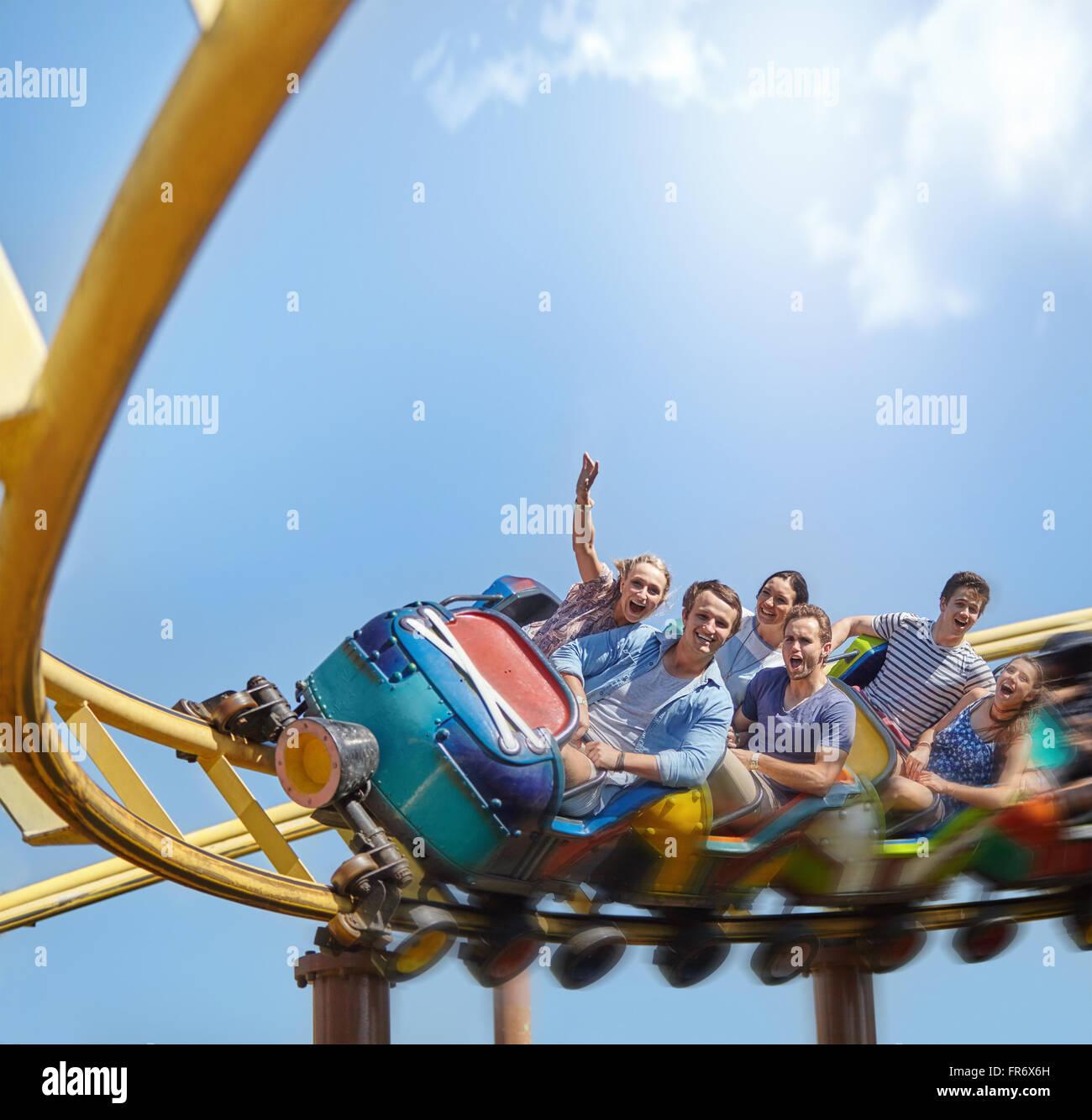 Jubelnde Freunde fahren Achterbahn im Freizeitpark Stockbild