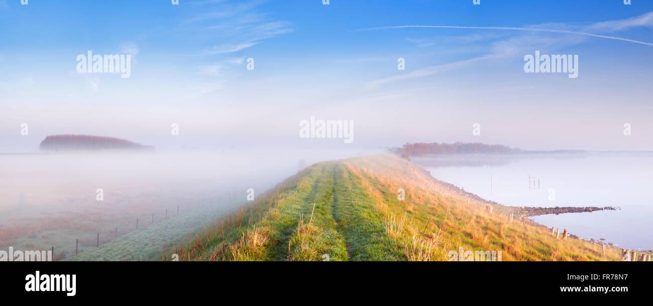 Eine typische holländische Polderlandschaft mit einem Deich entlang eines Sees. Am Veerse Meer in der Provinz Stockbild