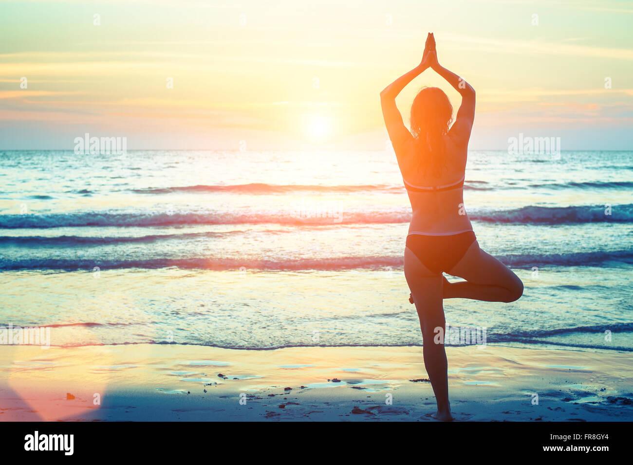 Silhouette-Yoga-Frau am Strand bei Sonnenuntergang. Stockbild
