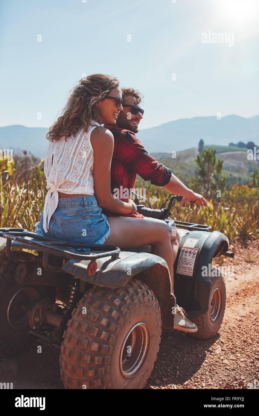 Porträt des jungen Mann und Frau in der Natur auf einer off-Road Fahrzeug. Junges Paar genießen ein Quad Stockbild