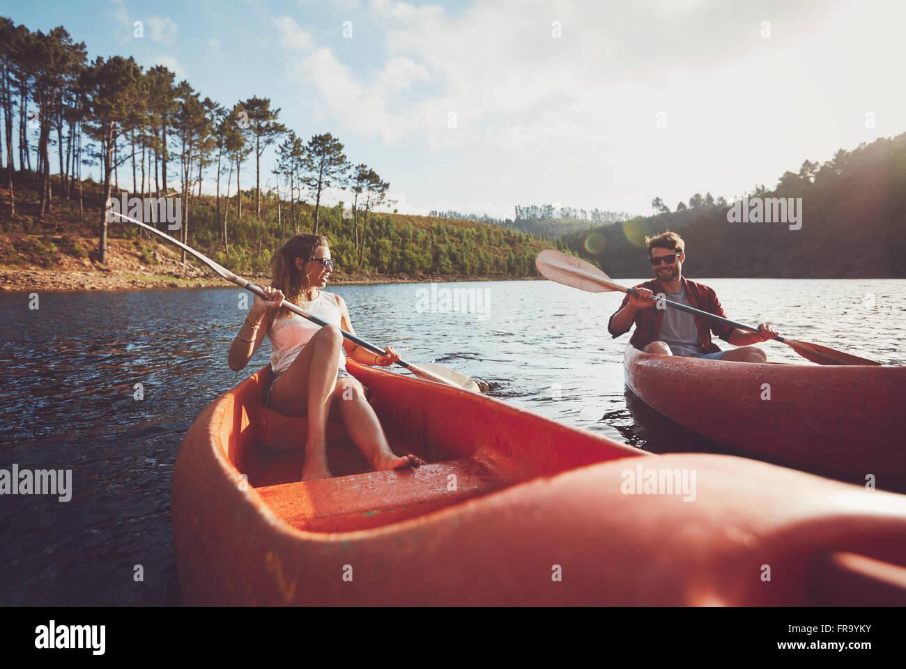 Junges Paar an einem See paddeln. Junge Kanuten an Sommertag am See rudern. Stockbild
