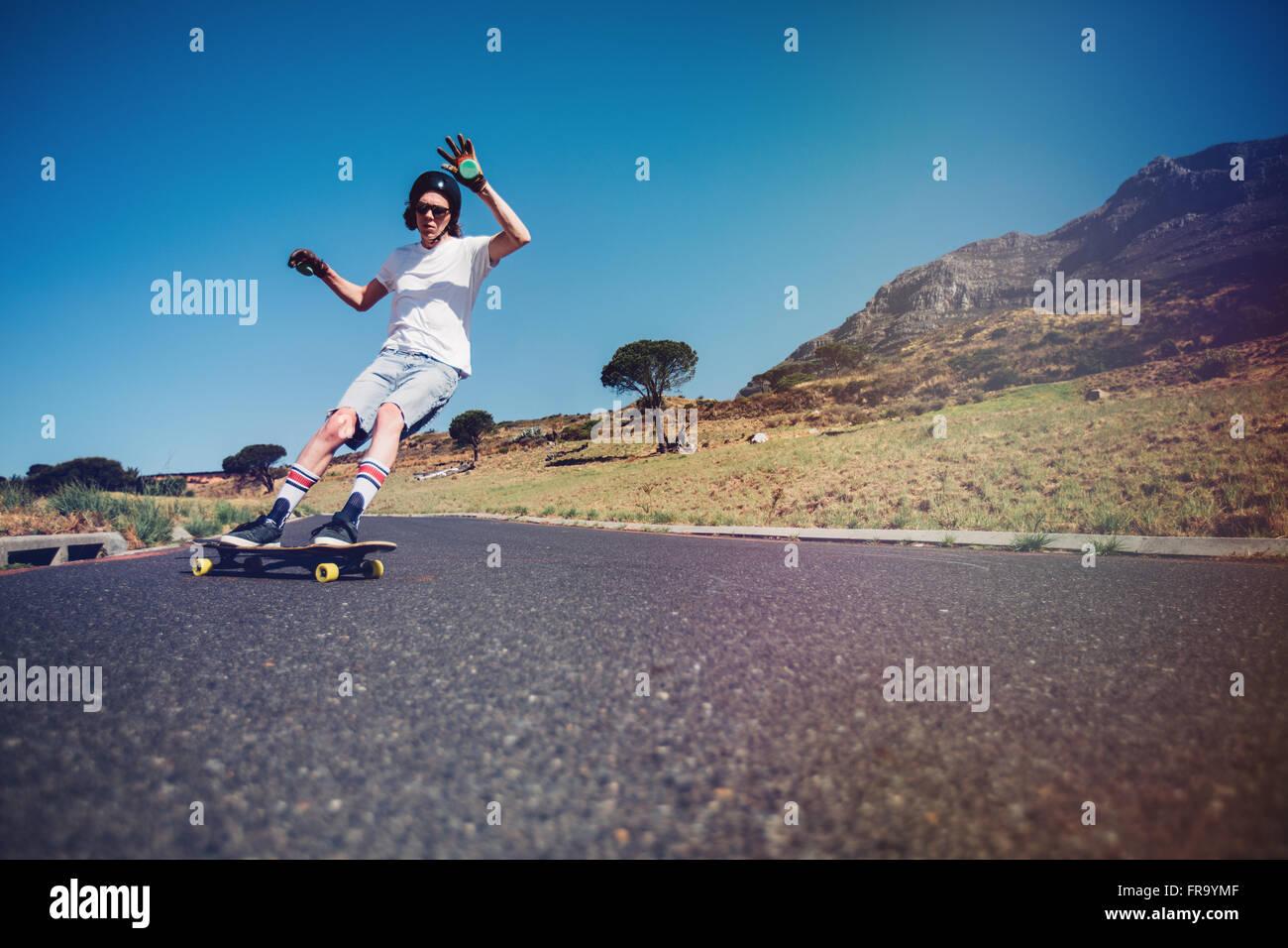 Junger Mann Longboarden auf einer Straße. Junger Mann mit Schutzausrüstung Schlittschuhlaufen auf Landstraße. Stockbild