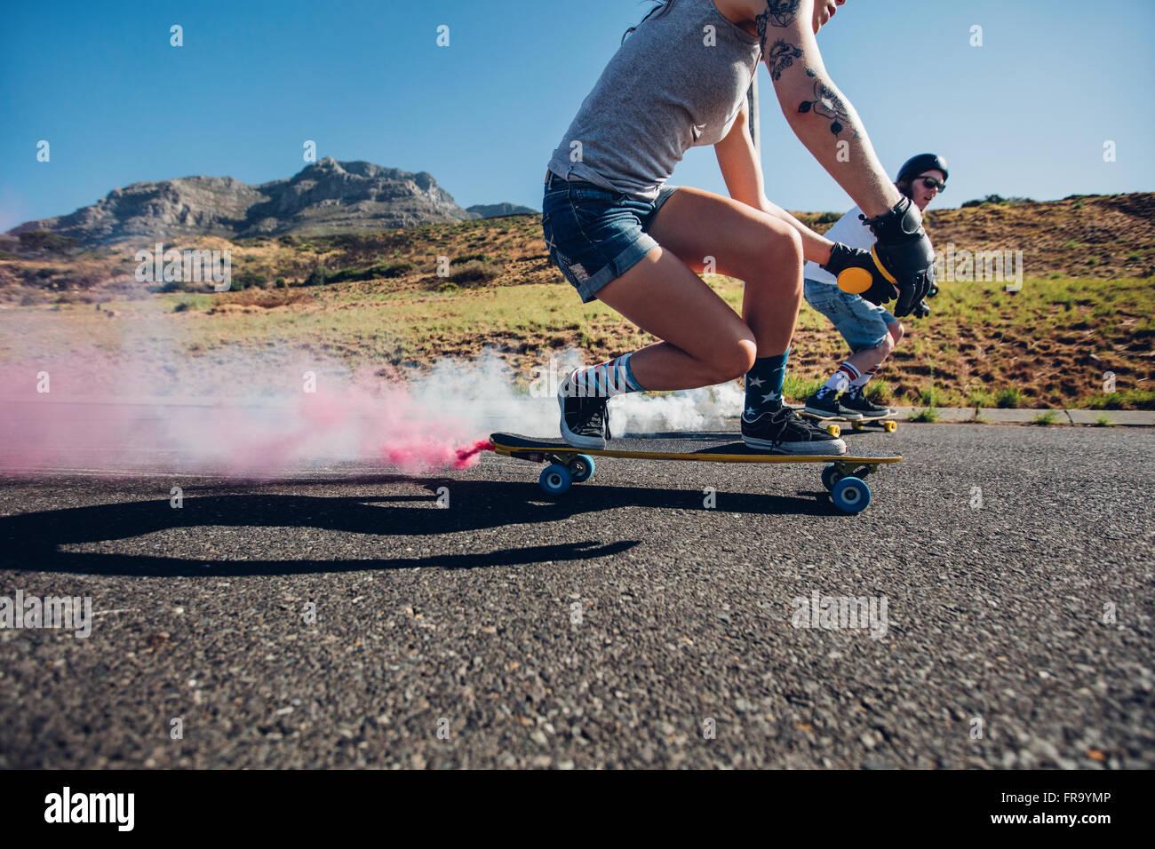 Mann und Frau Longboarden auf der Straße. Seitenansicht des jungen Menschen üben, Eislaufen im Freien Stockbild