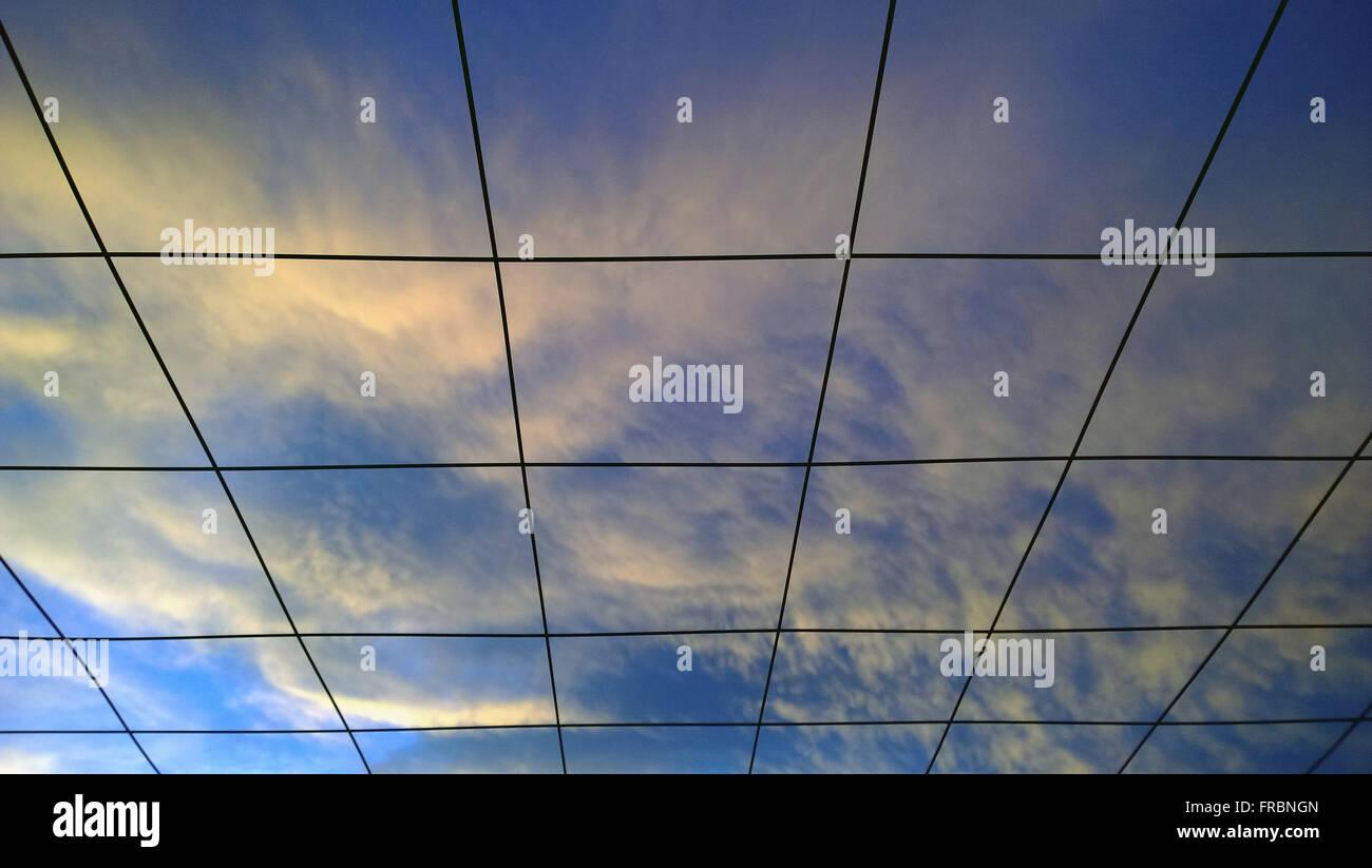 Himmel mit Wolken im Spätsommer am Nachmittag gesehen durch Gitter Stockbild