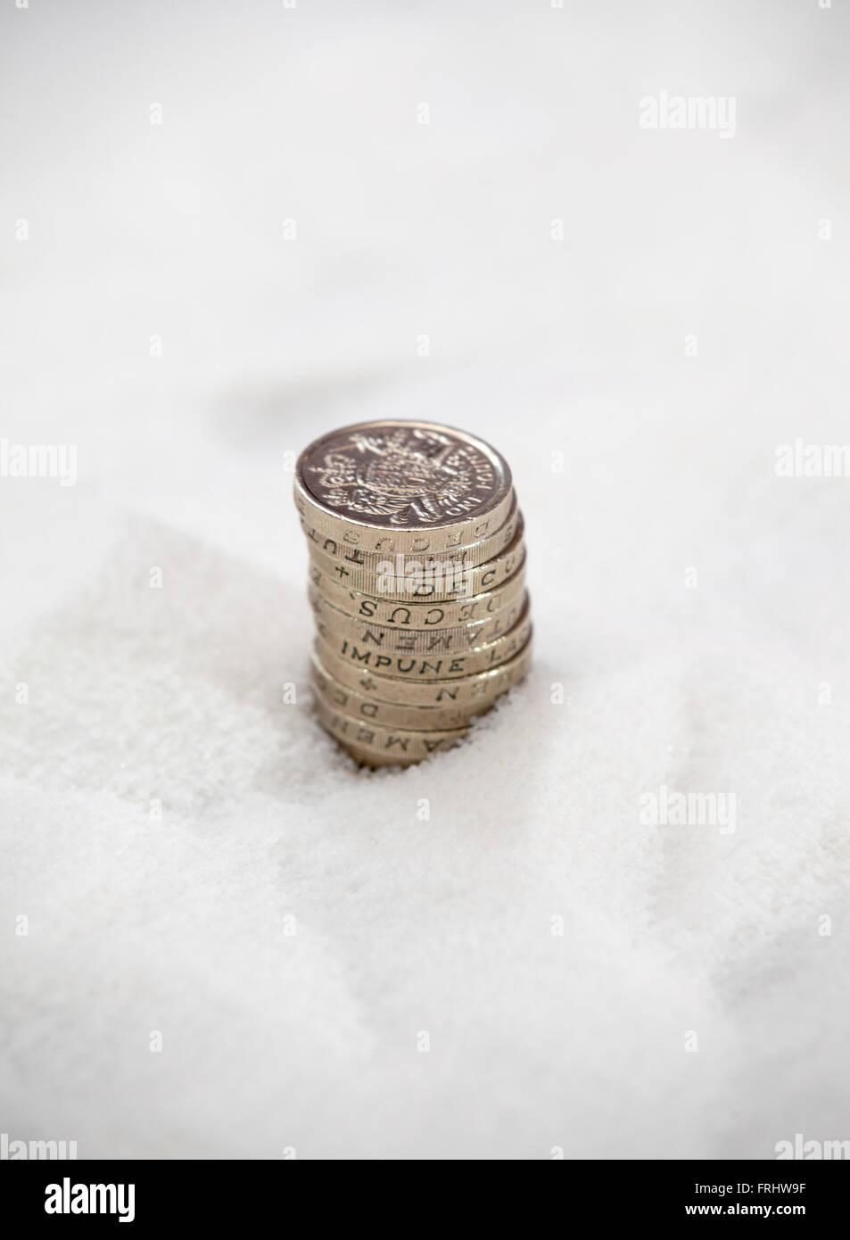 Ein Stapel von Pfund-Münzen, die Hälfte in Zucker beigesetzt Stockbild