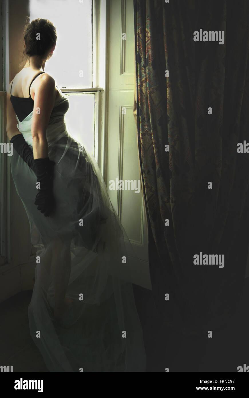 junge elegante Frau am Fenster im Altbau Stockfoto
