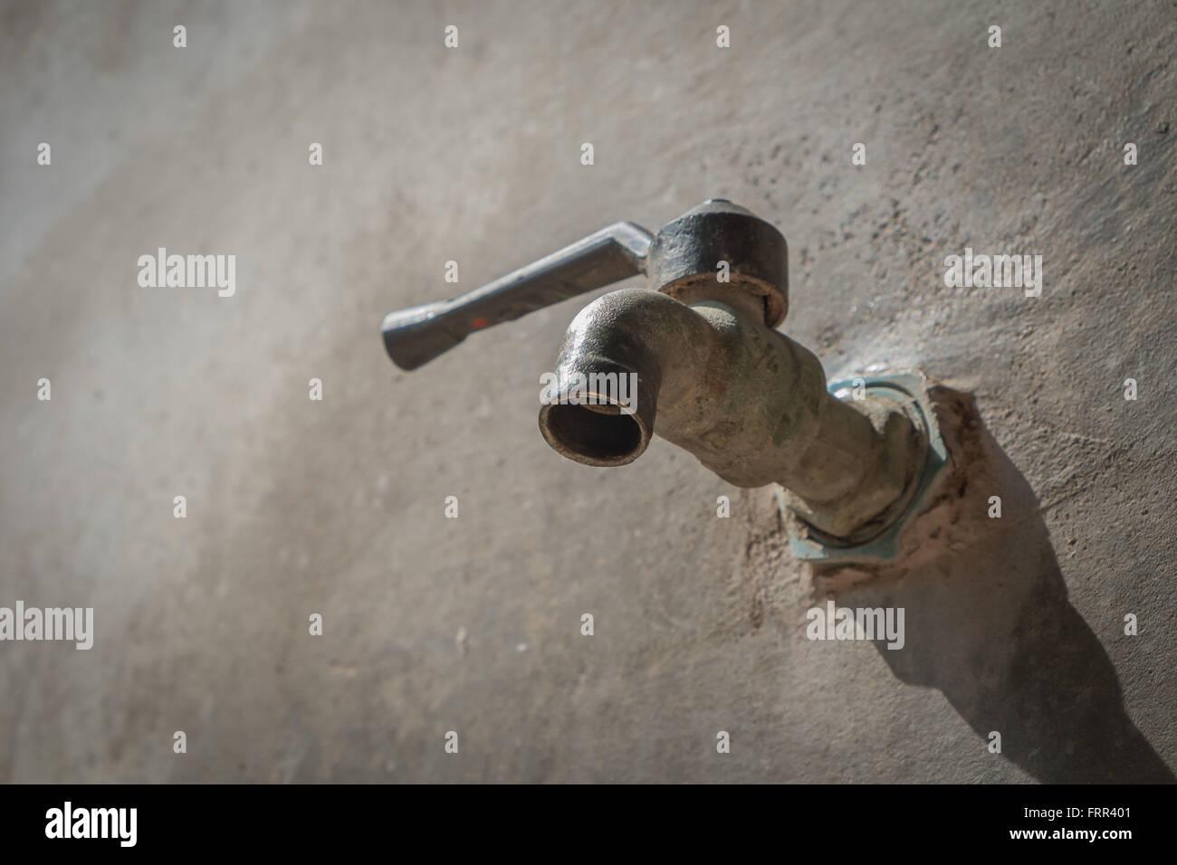 alter wasserhahn auf betonwand, speichern das wasserkonzept