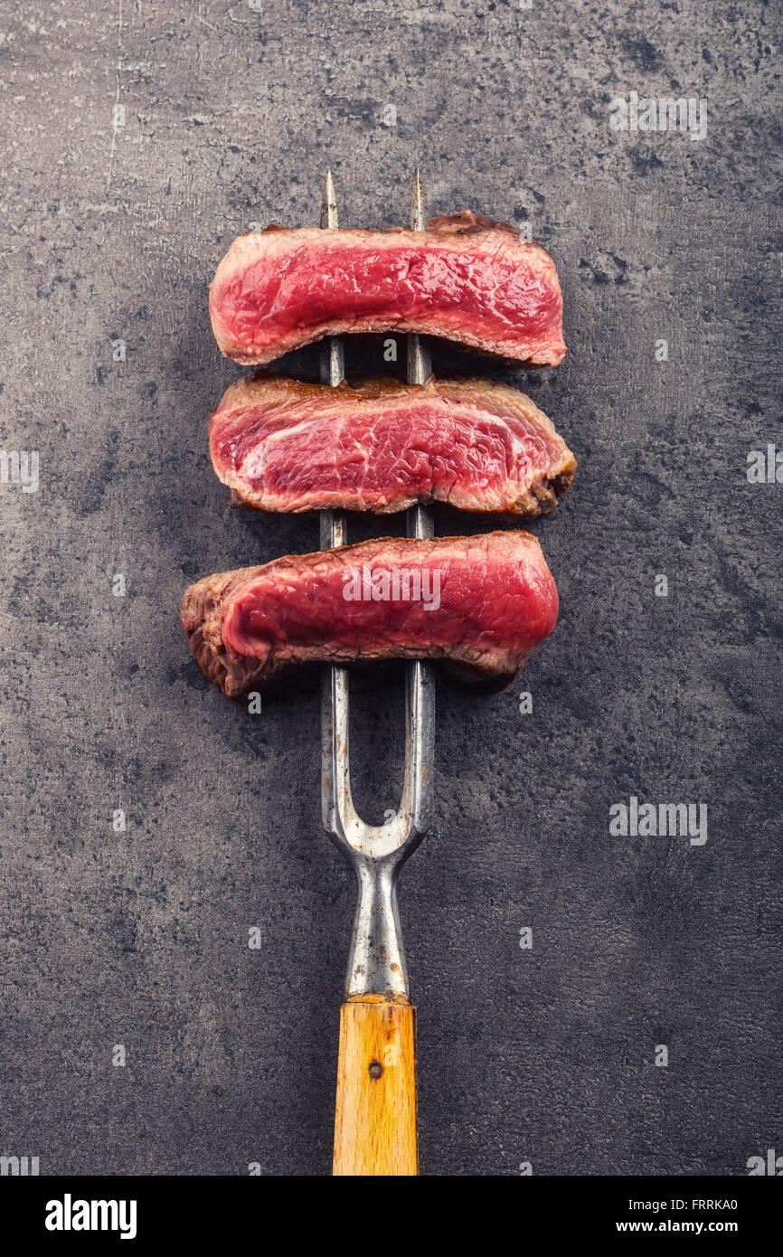 Steak. Grill Beefsteak. Scheiben vom Rind-Rumpsteak auf Fleischgabel auf konkreten Hintergrund. Stockbild