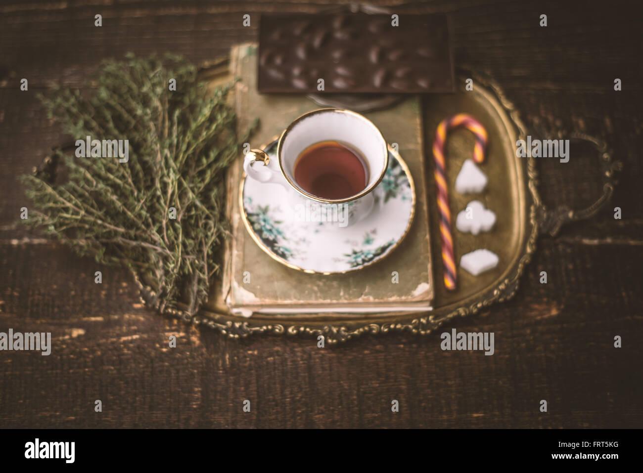 Tee-Set mit unscharfen Kraut und Schokolade auf dem Holztisch horizontale Stockbild