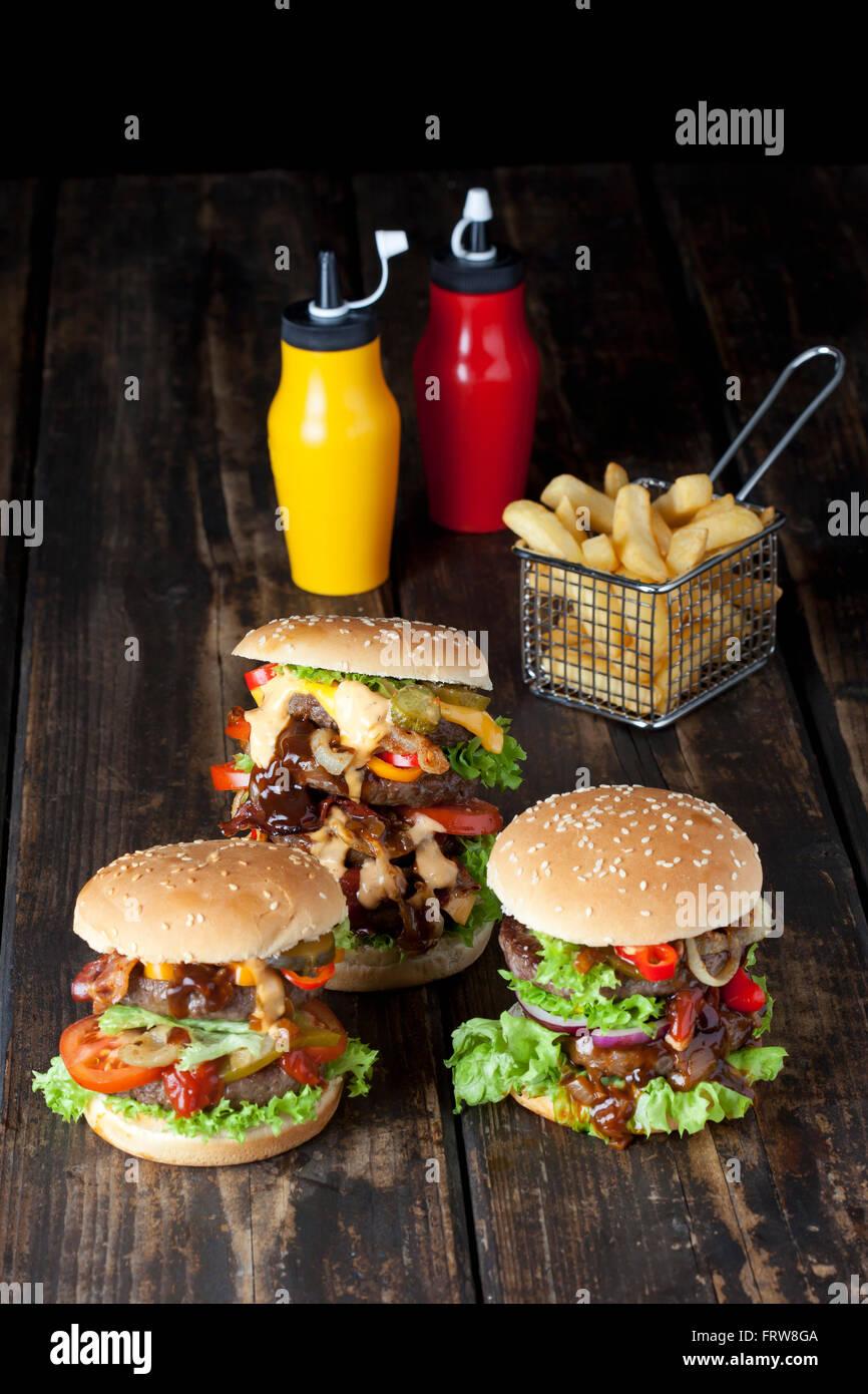 Großer Hamburger mit Pommes und Ketchup und Senf in Flaschen Stockbild