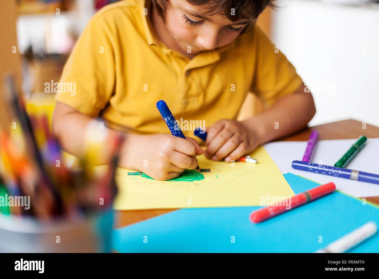 Kleiner Junge auf gelbem Papier zeichnen Stockbild