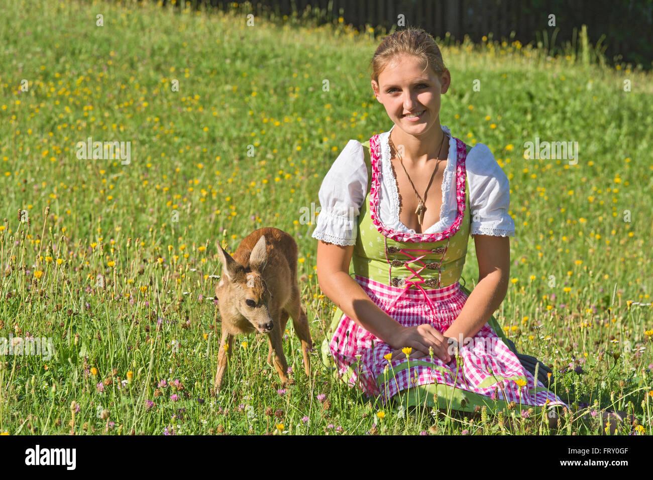Frau im Dirndl mit zahmen Faon in einer Blumenwiese, Tirol, Österreich Stockbild