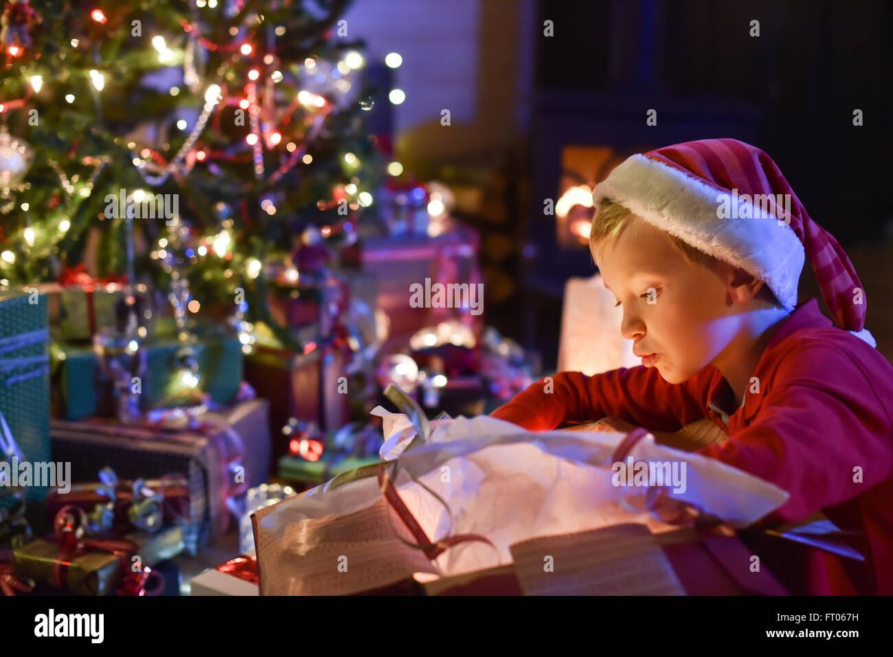 Schöner kleiner Junge mit einem Weihnachtsmann Hut öffnet ein ...