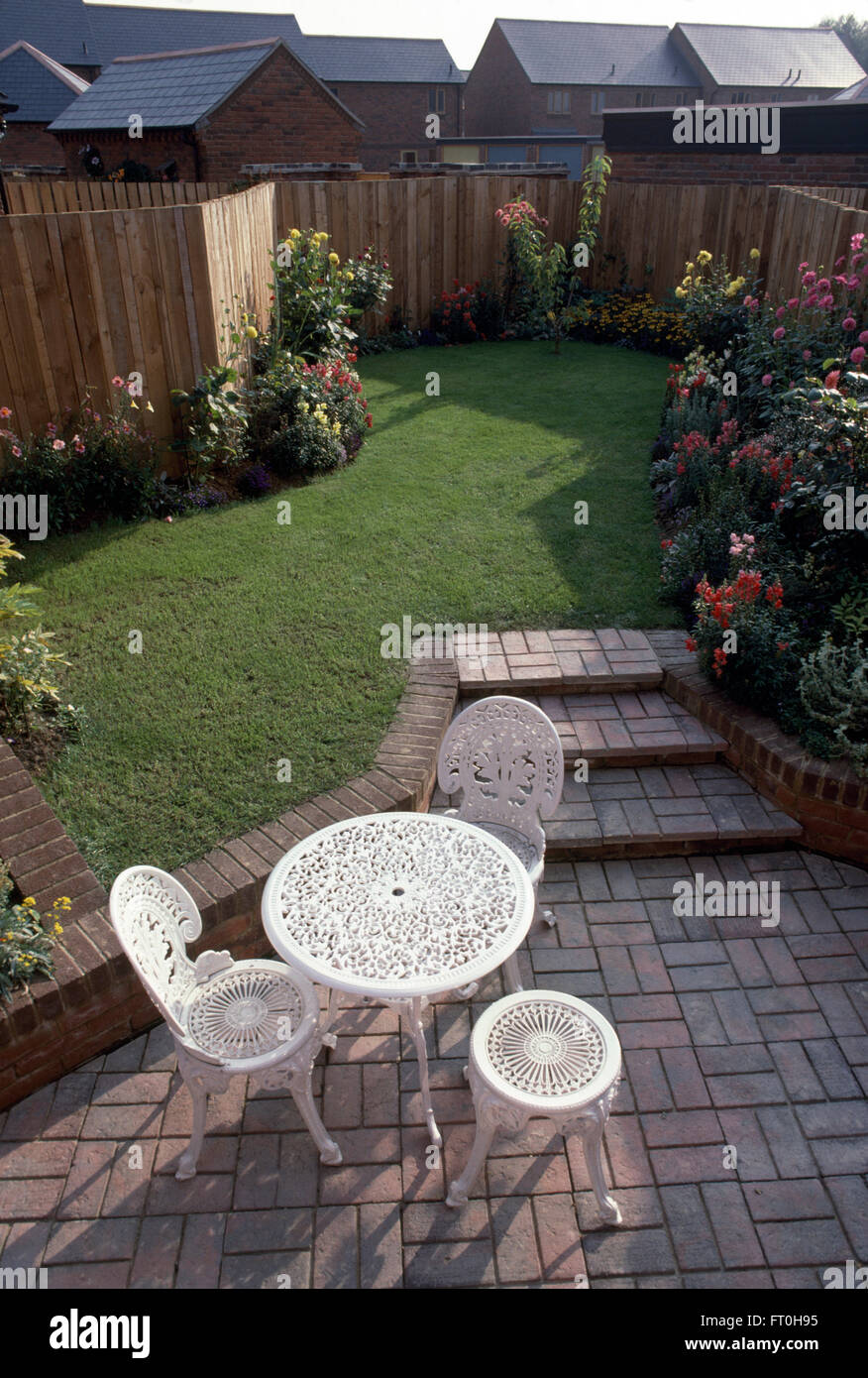 weißen schmiedeeisen tisch und stühle auf gepflasterte terrasse mit