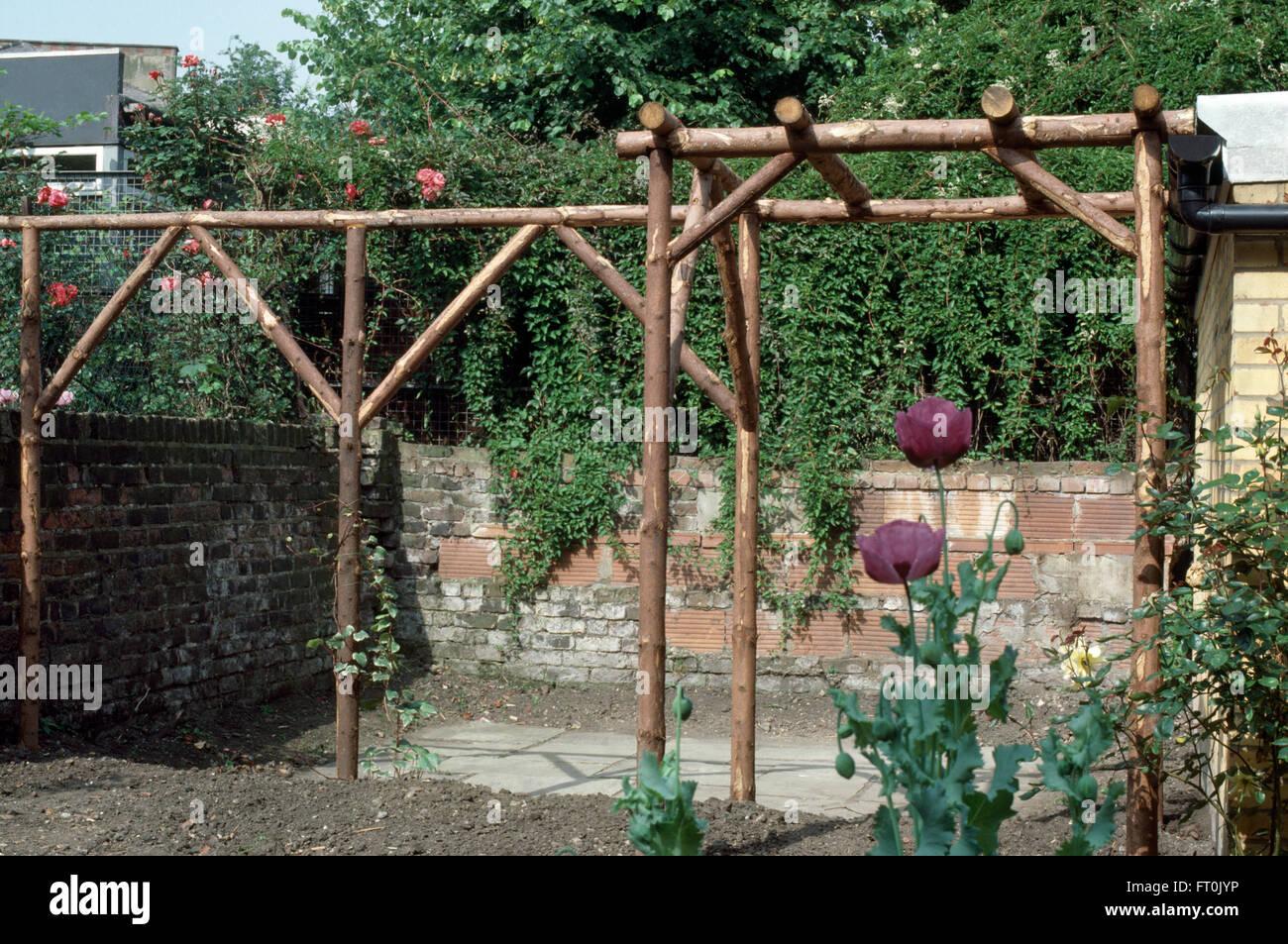 ein neu gemacht rustikale pergola aus holz in einem garten renoviert