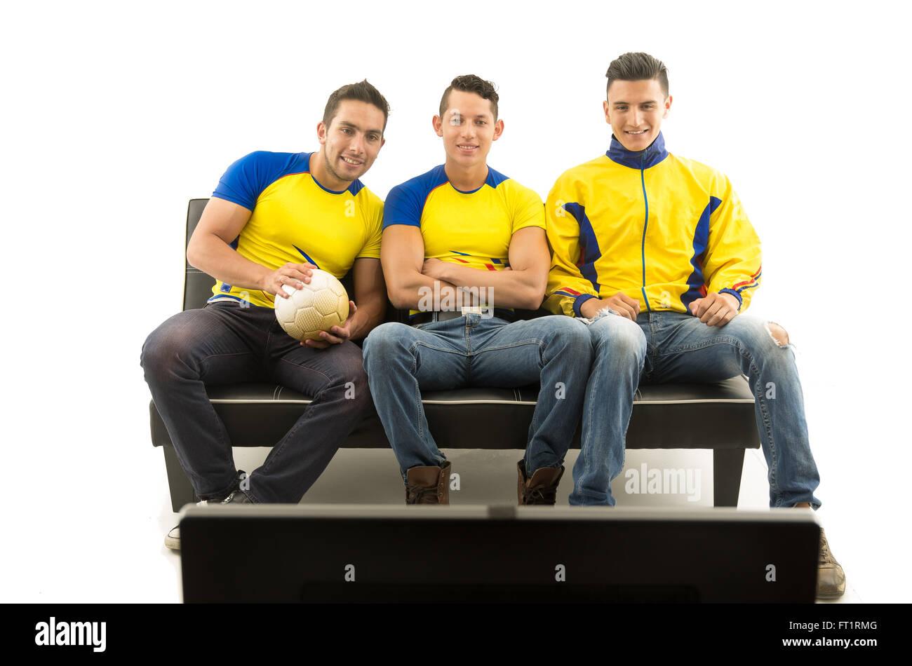 drei freunde auf sofa tragen gelbe sporthemden fernsehen mit begeisterung wei er hintergrund. Black Bedroom Furniture Sets. Home Design Ideas