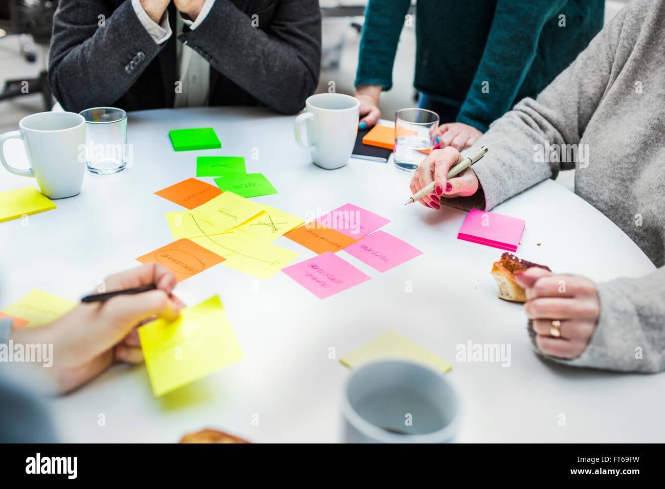 Bild von Geschäftsleuten mit Klebstoff Noten am Tisch im Kreativbüro beschnitten Stockbild