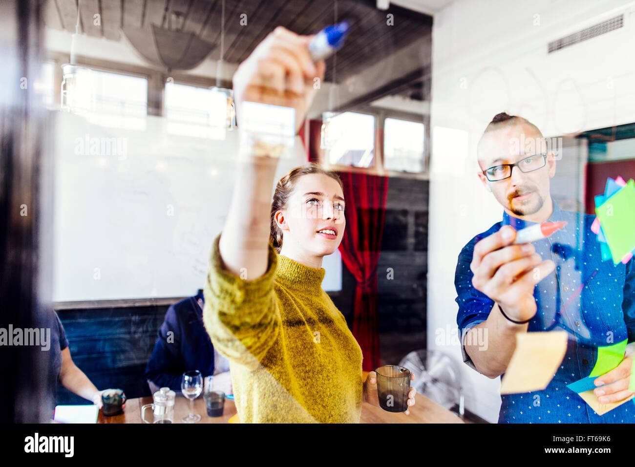 Kreative Business-Leute, die schreiben auf Glas Wand im Sitzungsraum Stockbild