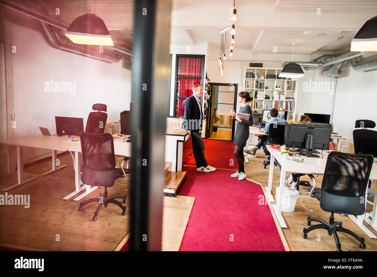 Geschäftsleuten stehen im Büro diskutieren Stockbild
