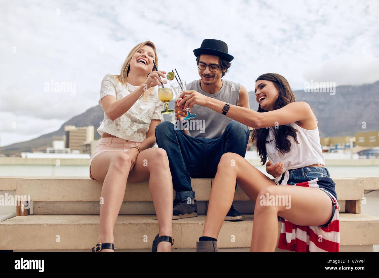 Glückliche junge Freunde sitzen auf Stufen und Toasten Cocktails. Junge Menschen mit einer Party auf dem Dach. Mann Stockfoto