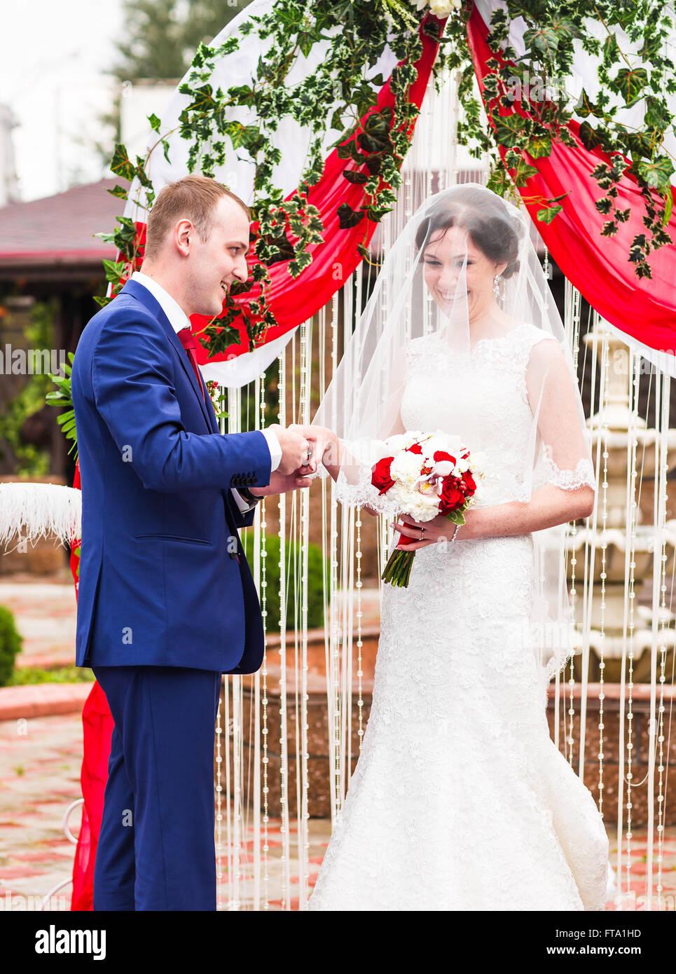 paar in der Kleidung Hochzeit Ringe mit Bogen auf Hintergrund ...