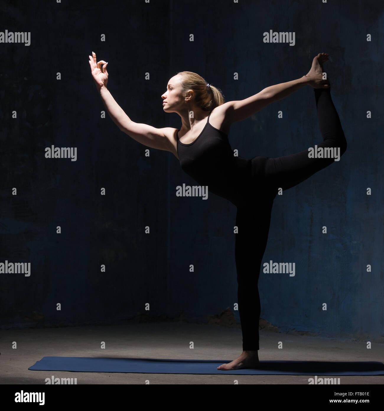 Schön passen sportliche junge Frau drinnen dunkel blaue Wand Grunge erarbeiten. Im Backbend Natarajasana Modell Stockbild