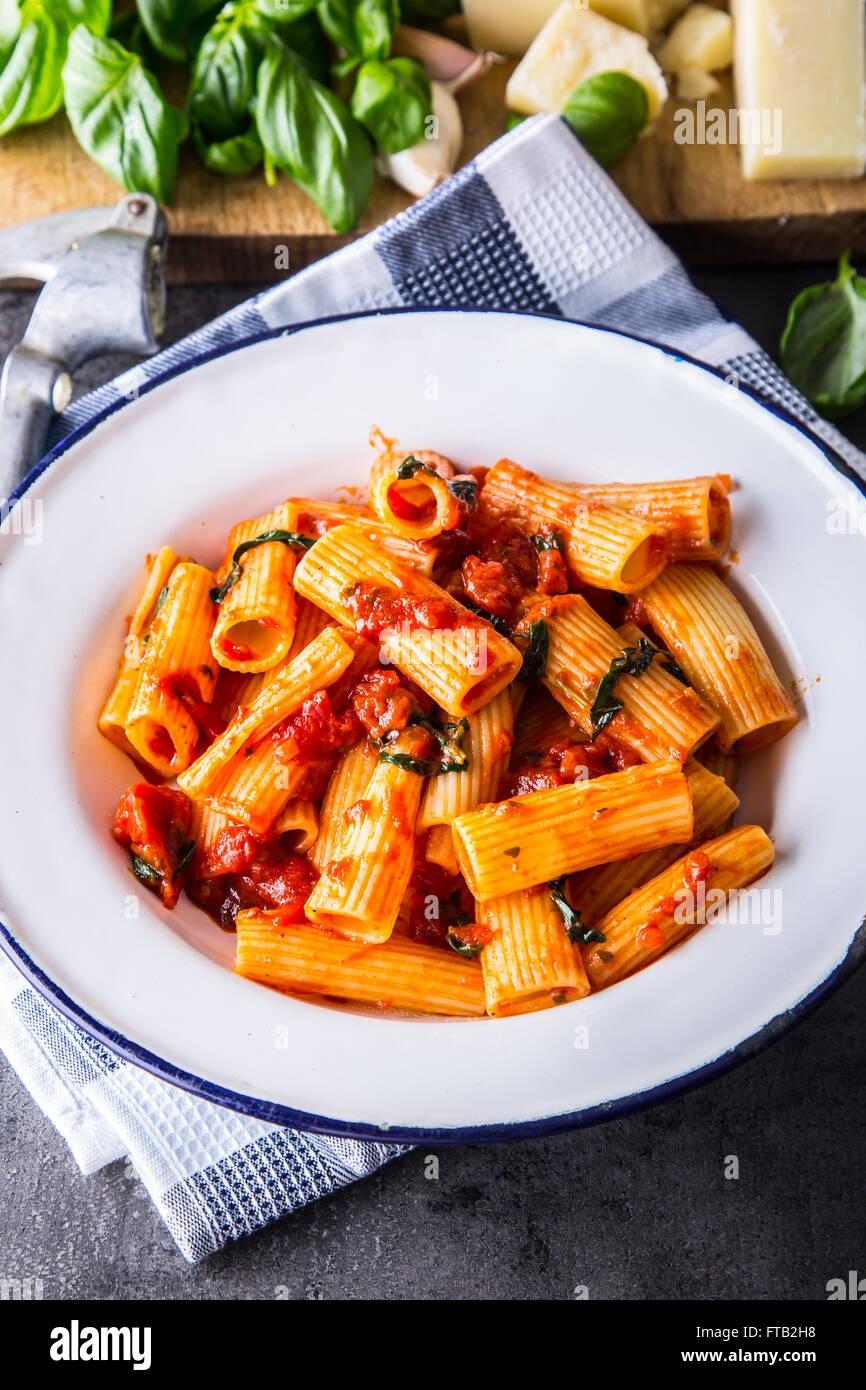 Nudeln. Italienische und mediterrane Küche. Pasta Rigatoni mit Tomaten-Sauce Basilikum Blätter Knoblauch Stockbild