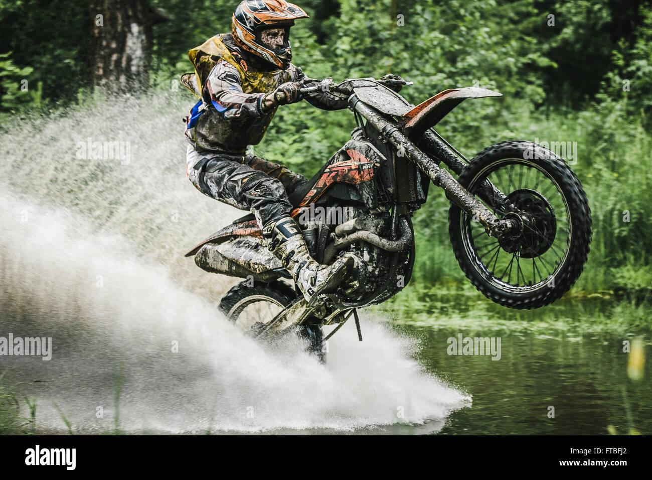 """Motocross-Fahrer unter den Spray von Wasser während des Rennens Ural Cup Enduro """"Stein Gürtel 2015"""" Stockbild"""