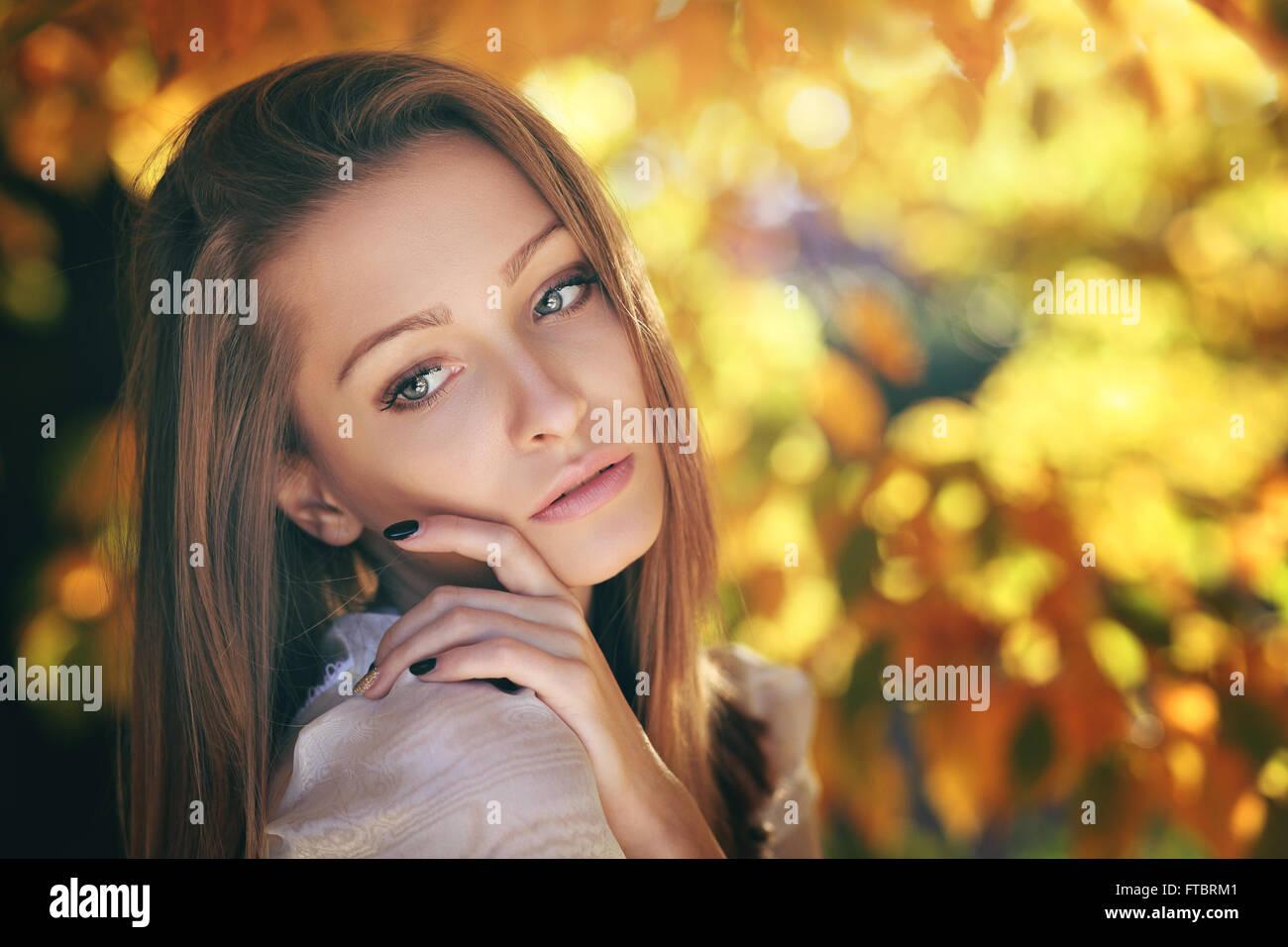 Warme Herbst-Porträt einer jungen Frau. Goldene Blätter hinter Stockbild