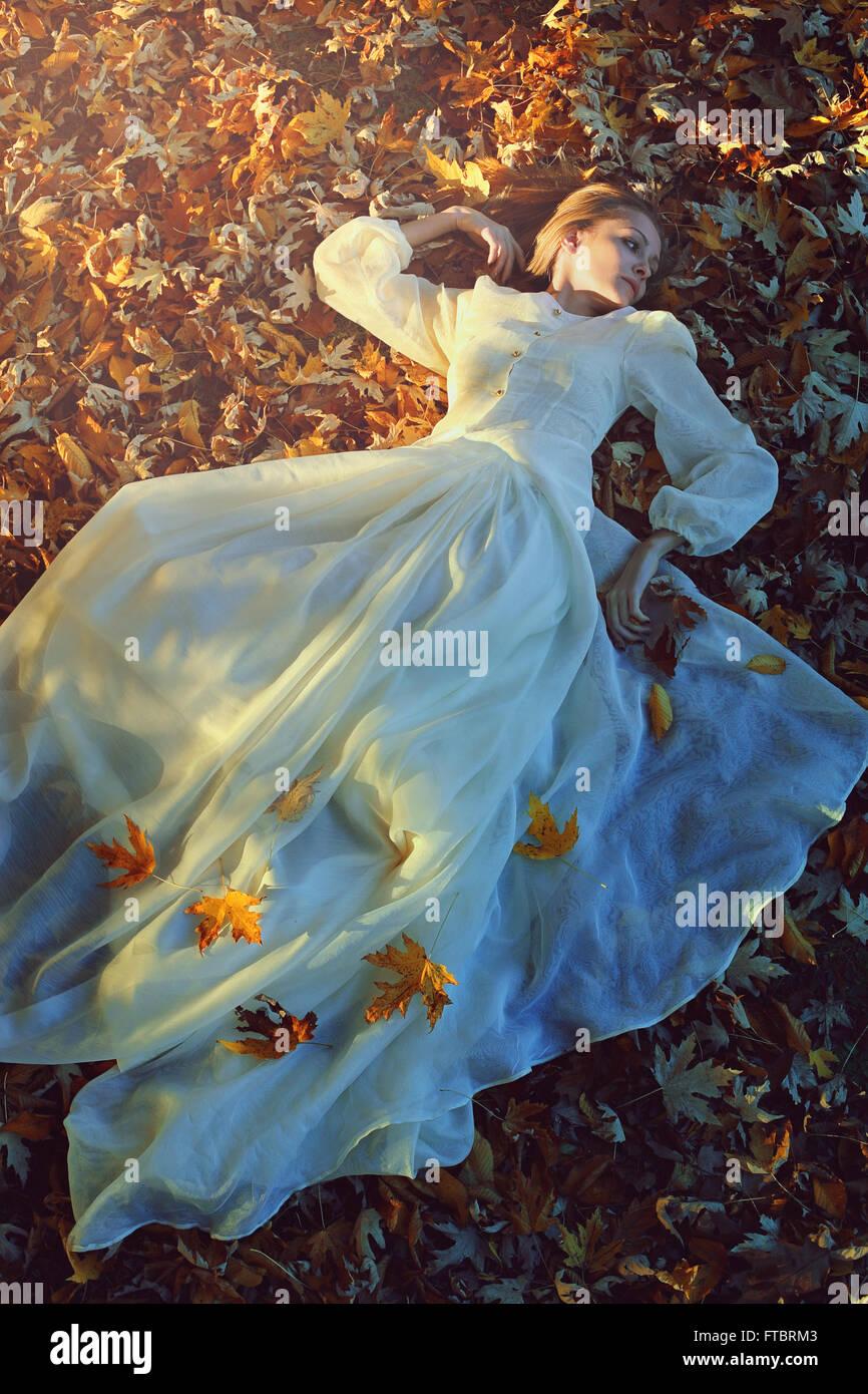 Schöne Frau mit viktorianischen Kleid auf einem Bett aus Blättern. Trauer und Einsamkeit-Konzept Stockfoto