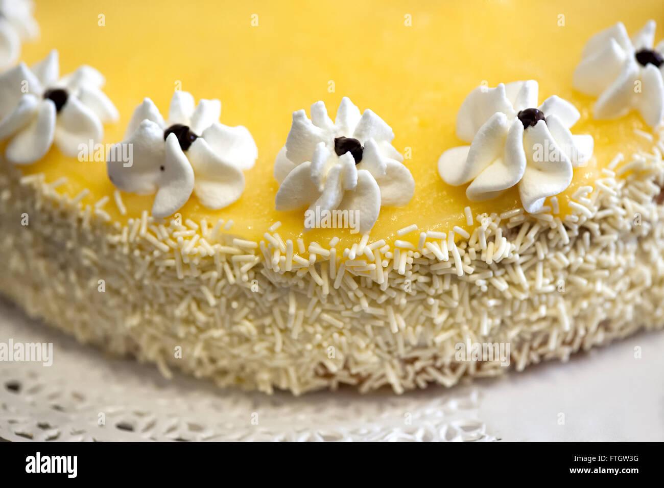 Hohen Winkel schließen sich kulinarische Stillleben mit hausgemachte Zitronenkuchen mit Zuckerguss Blumen geschmückt Stockbild