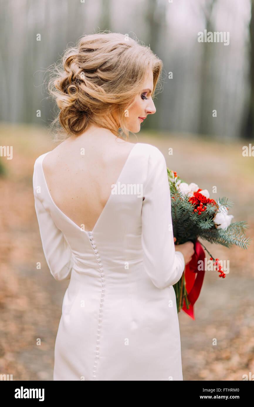 Schöne blonde Braut in lange Spitze Hochzeitskleid holding Bouquet ...