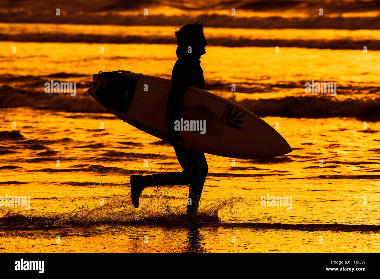 Die Silhouette eines Surfers läuft entlang der Küste auf Fistral Beach bei Sonnenuntergang einen farbintensiven Stockbild