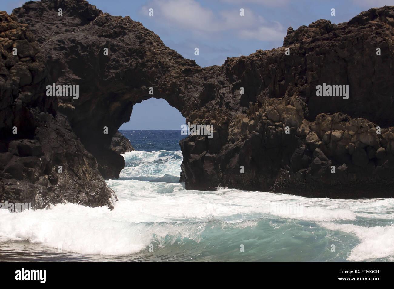 Vulkangestein durchbohrt durch die Kraft des Wassers auf der Insel Trinidad im Atlantischen Ozean Stockbild