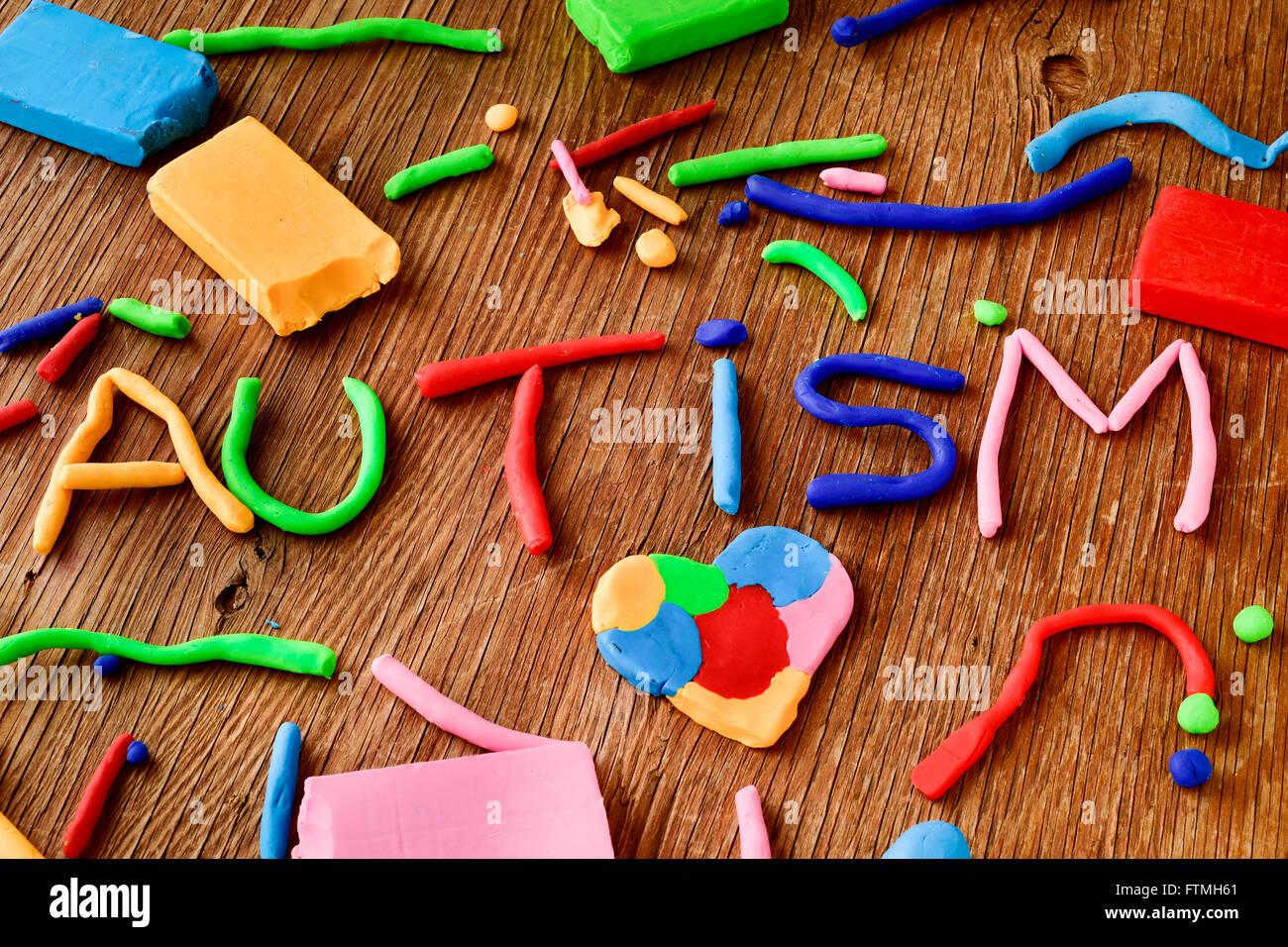 das Wort Autismus aus Knetmasse in verschiedenen Farben auf einer rustikalen Holzoberfläche gefertigt Stockbild