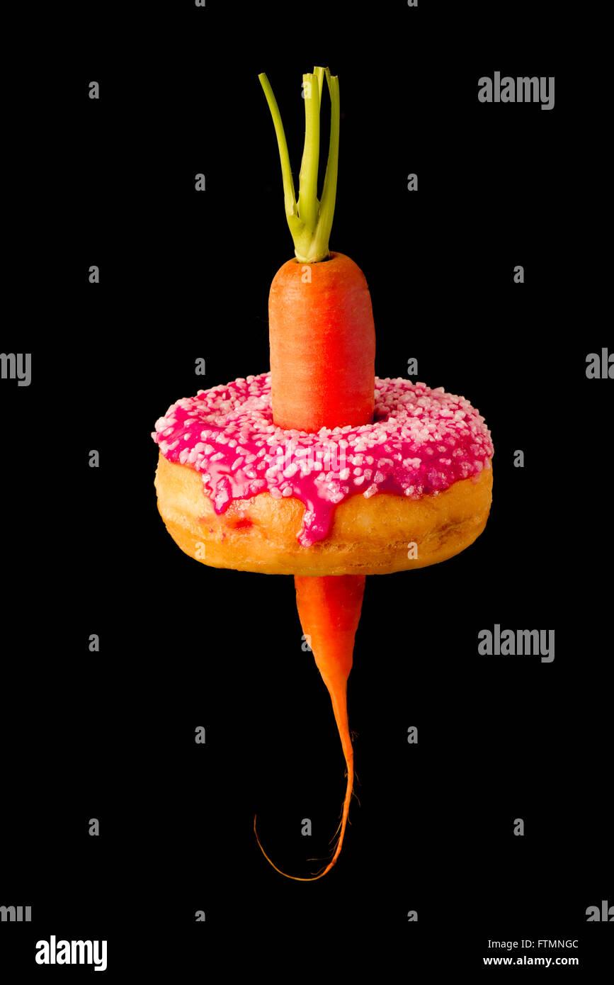 Karotte durch Donut demonstrieren gesunde und ungesunde Ernährungsgewohnheiten und Ausbau Taillen / Fettleibigkeit. Stockbild
