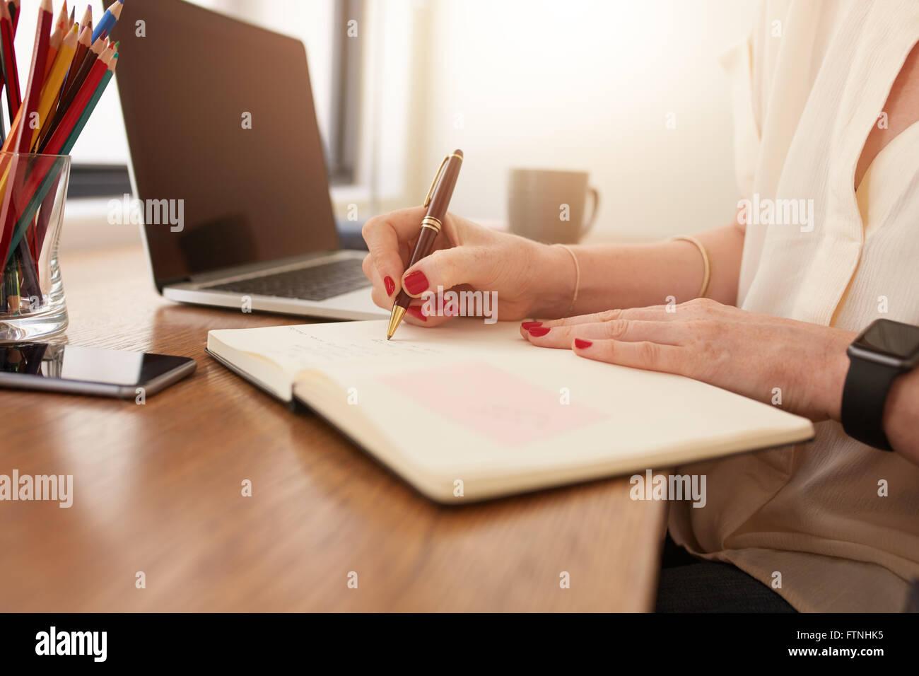 Schließen Sie herauf Bild der Frau sitzt an ihrem Schreibtisch und Schreiben von Notizen. Geschäftsfrau Stockbild