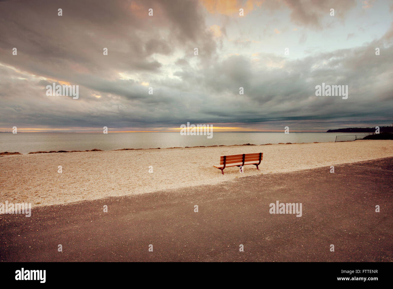 Leere Bank am Strand Stockfoto
