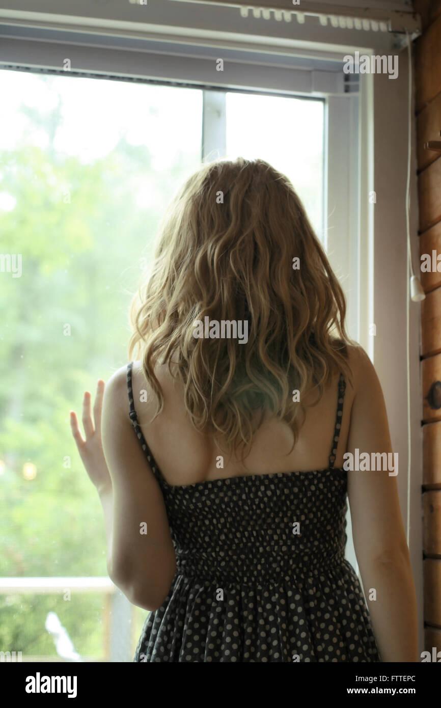 Frau am Fenster stehend Stockbild