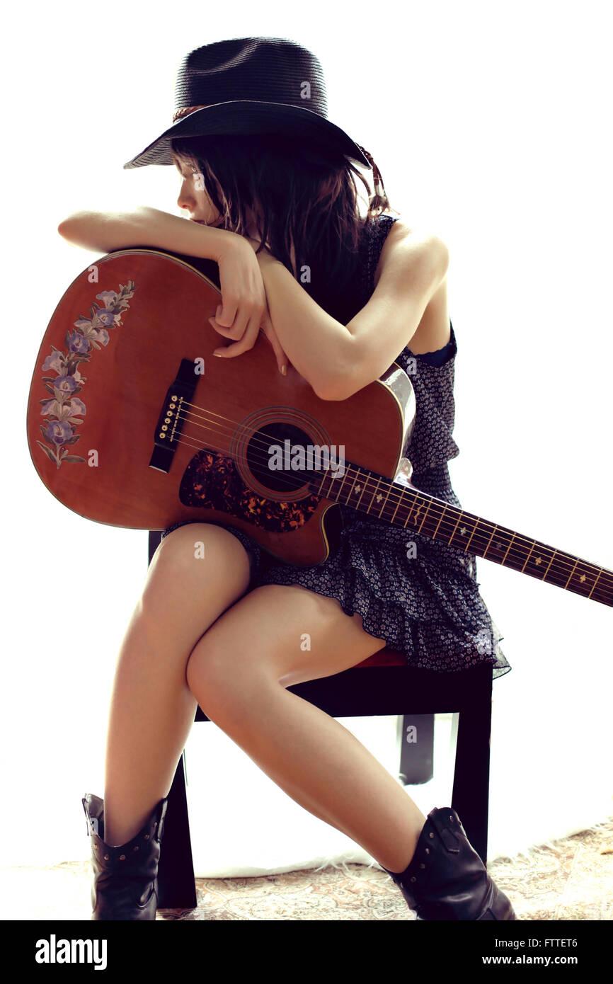 Brünette sitzen, ruhen auf Gitarre Stockbild